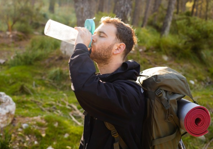 young male hiker drinking water his | non potable water
