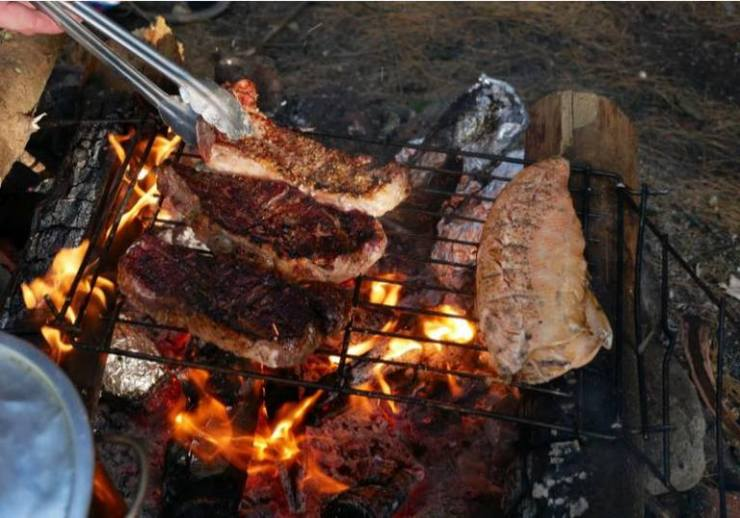 Cooking steak and fish over campfire | campfire cooking