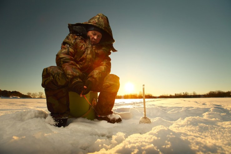 Fisherman on a lake at winter sunny day | ice fishing tips for perch