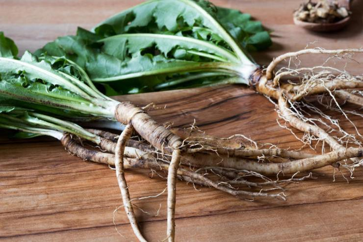 Dandelion roots with leaves on a wooden cutting board | how to make dandelion tea