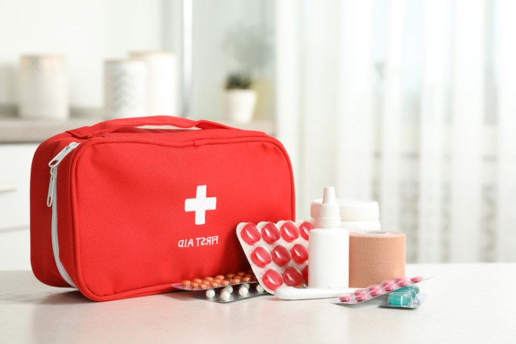 First aid box with pills on the table inside | Emergency bag checklist