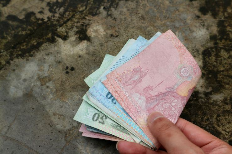 Hand holding money in dirty stone floor | Contents of the emergency bag