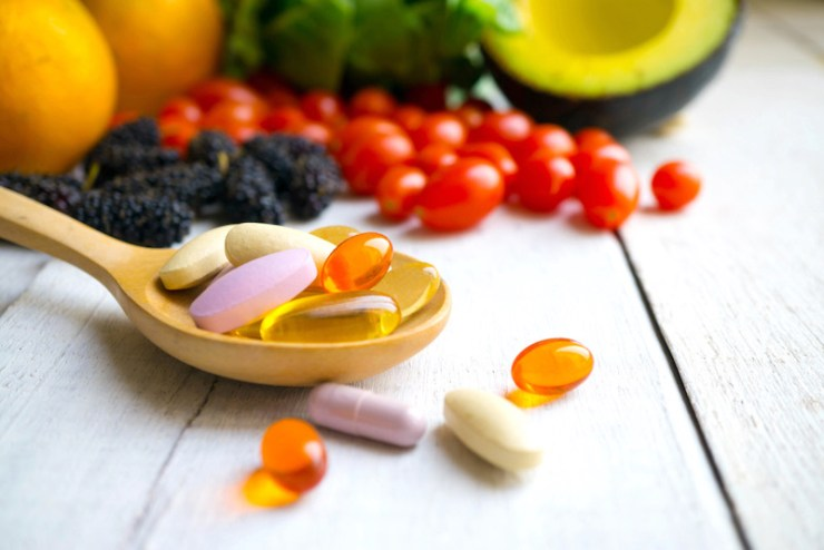 Pills and capsules in wooden spoons with fresh fruits what to pack in an emergency bag