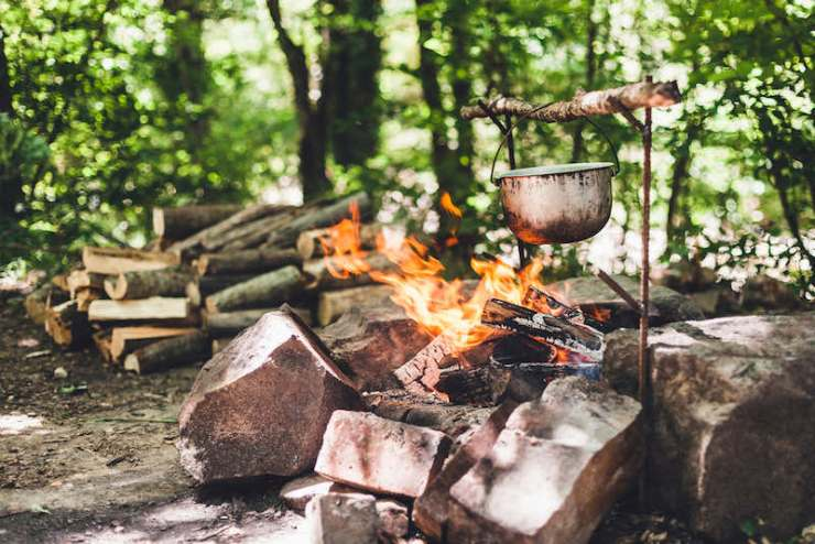 The pot burns at night near the tent in the forest what to pack in an emergency bag
