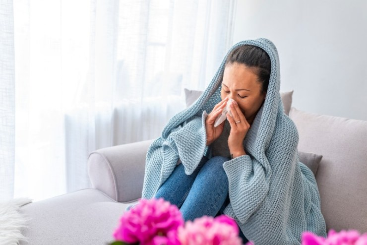 Woman sneeze on bed. Flu. Young woman got nose allergy, flu sneezing nose sitting at home-shock