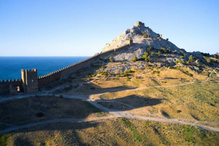 An ancient defensive wall that runs along the crest of a mountain on the seashore-terrain
