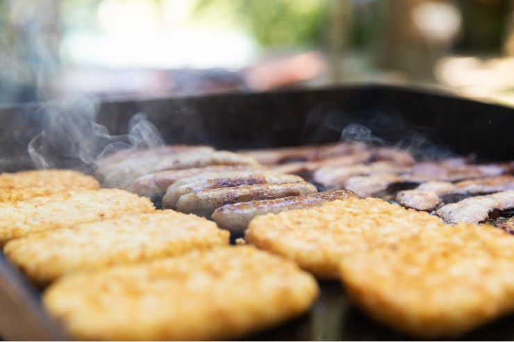 Bacon, sausage and hasbrowns cooking on a grill for breakfast at camp-favourite camping recipes