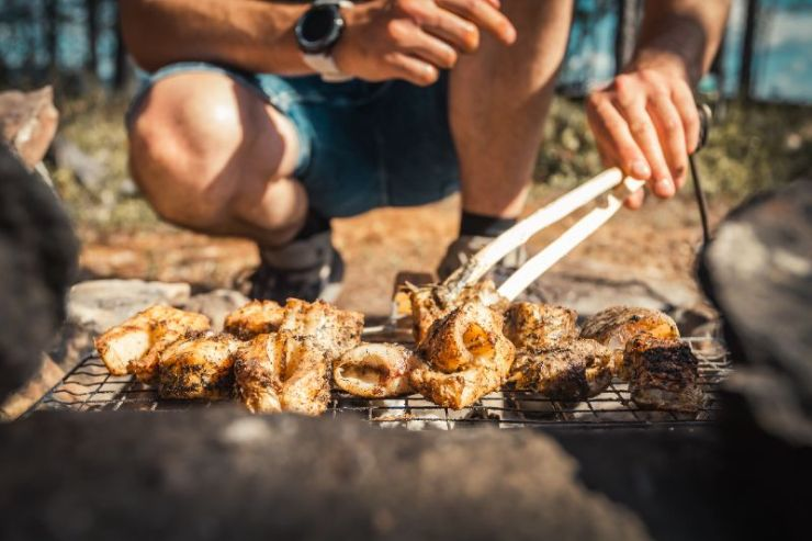 Cooking fish steaks over open fire while camping in nature-traditional camping food