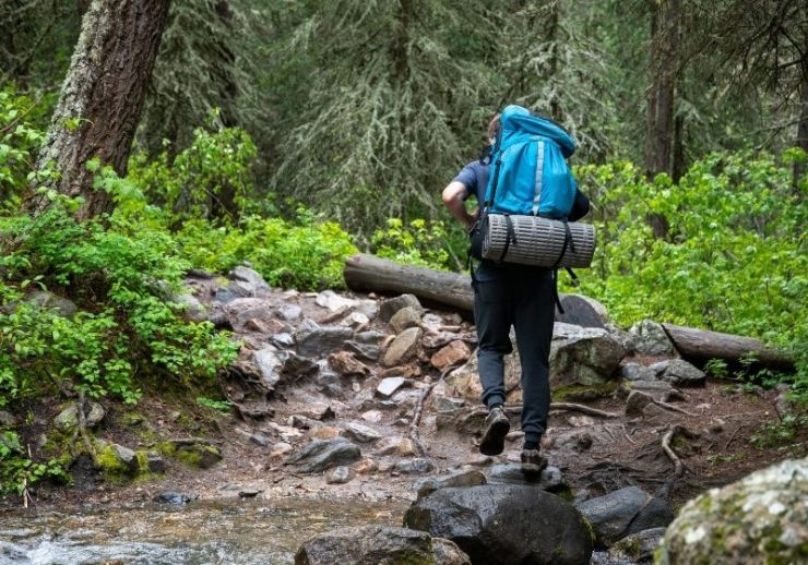 Man walking on rocky terrain | Tips to Help You Camp in the Rain