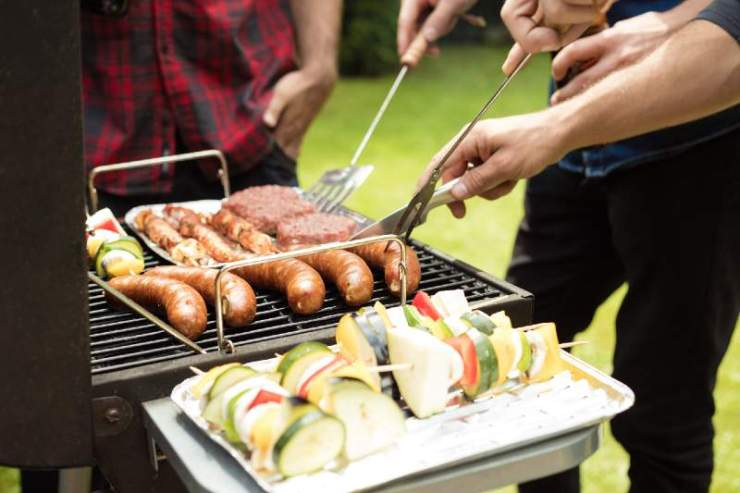Outdoor shot of three friends enjoying barbecue party, grilling sausage, burgers and vegetable skewers-camping food hacks