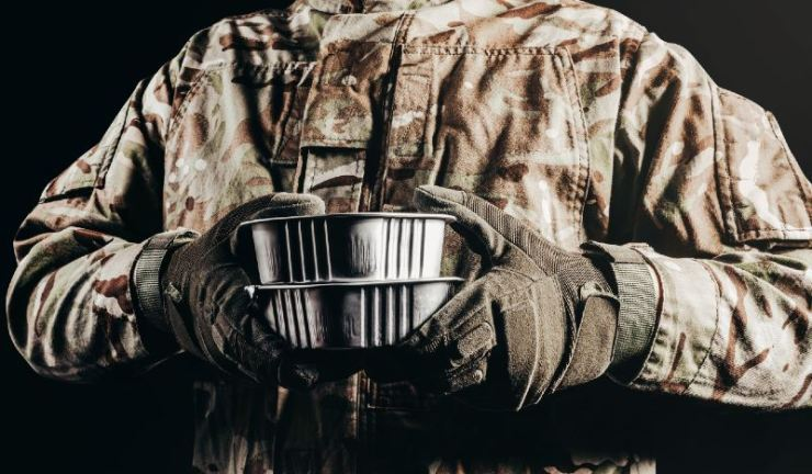 Photo of a soldier in camouflaged uniform and tactical gloves with canned MRE-DIY MREs