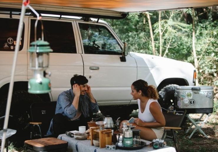 Positive multiethnic friends sitting at table near van | Tips to Help You Camp in the Rain