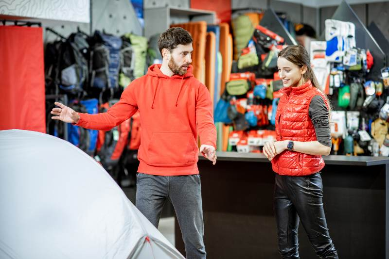 Salesman selling camping equipment to a young woman client in the sport shop | best camping tents