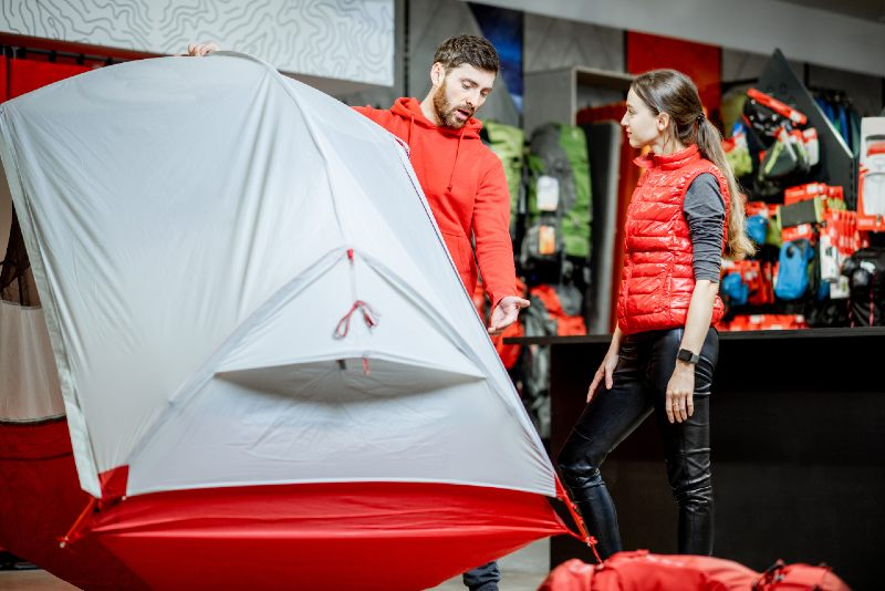 Salesman selling camping equipment to a young woman client in the sport shop-tent