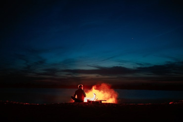 Silhouette of tourist around campfire at night on the river shore-Camping Without Electricity