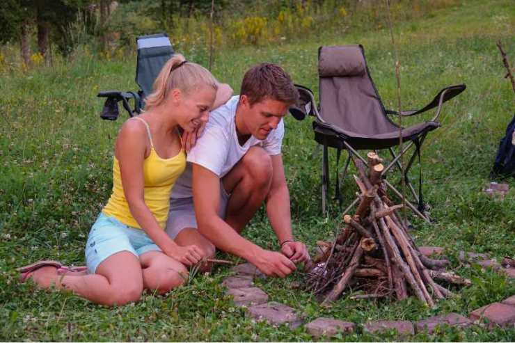 Smiling woman leans on her boyfriend who is lighting up the campfire by their tent-campfire