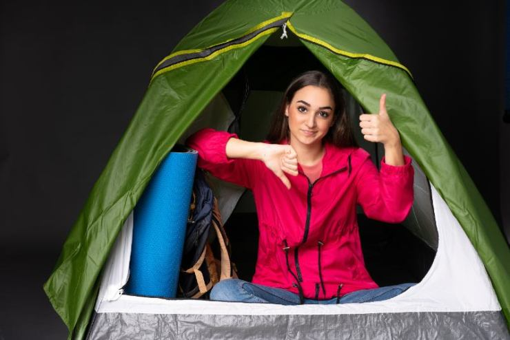 Young caucasian woman inside a camping green tent making good-bad sign | best camping tents