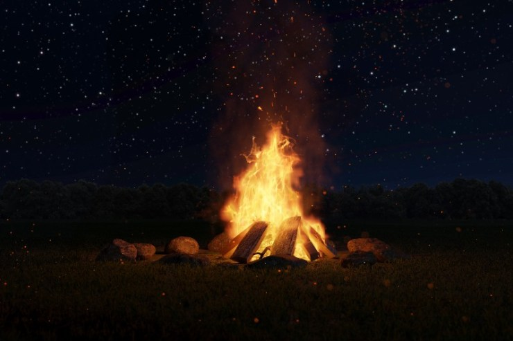 big bonfire with sparks and particles in front of forest and starry sky-Types of Campfires