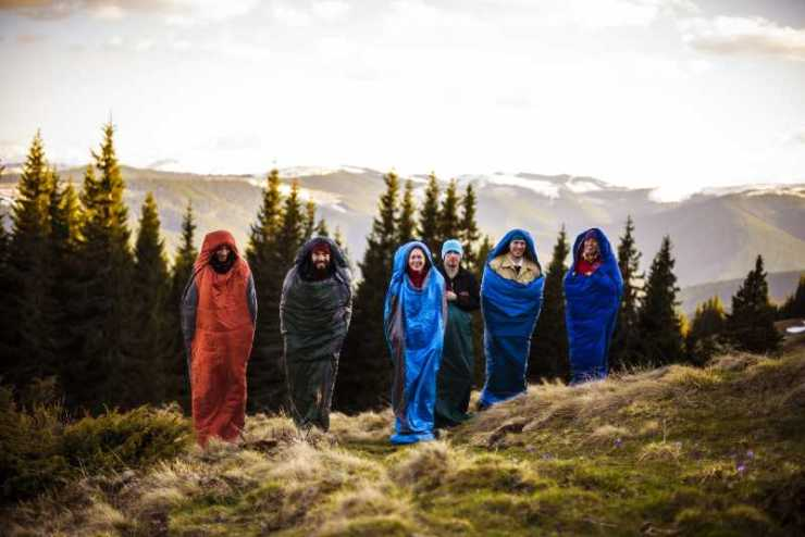 cheering group of hikers jumping in sleeping bags outdoors in mountains during the sunset-sleeping bag