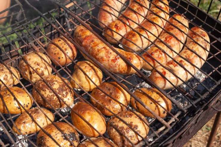 sausages fried at the stake with potatoes. delicious camping lunch-classic camping food