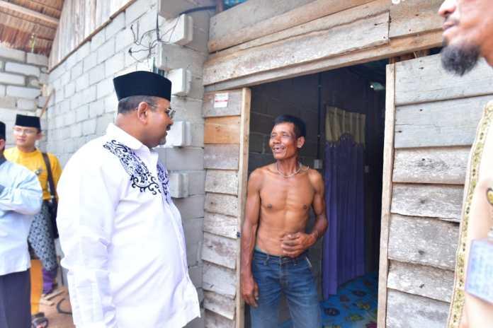 Bupati Karimun Aunur Rafiq berbincang dengan salah seorang warga penerima bantuan program rehabilitasi rumah tak layak huni di Kecamatan Ungar, Jumat (17/1/2020). Foto Suryakepri.com/istimewa