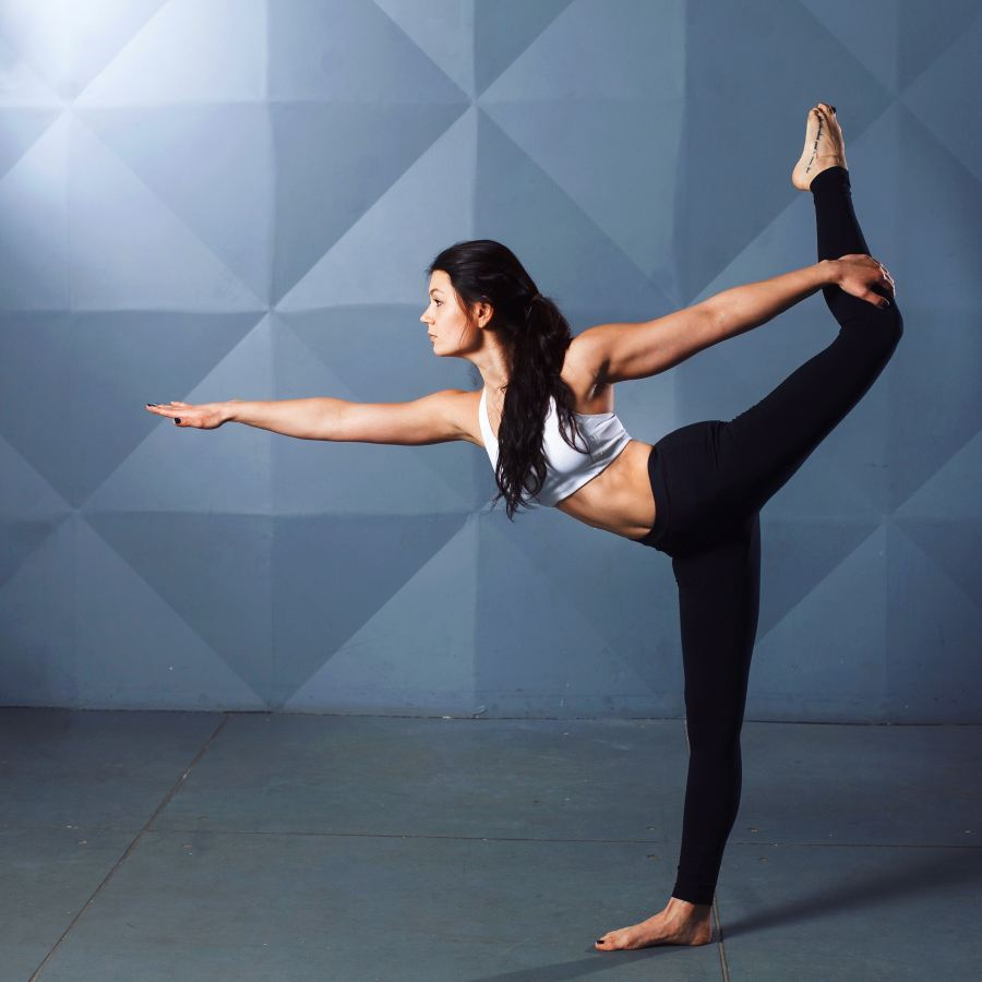 Increased balance, one of several exercise benefits. Woman is balanced  with one leg stretched out behind her. l