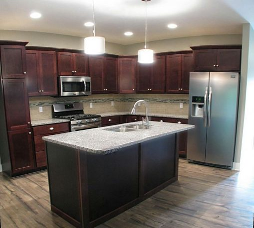 Another view of the main level efficient kitchen with center island and laminate floor.