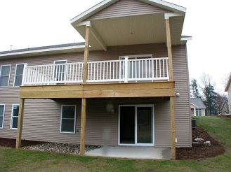 2433 Back of home showing covered deck and uncovered deck with cement patio below