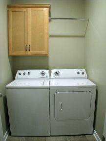 2506 Main floor laundry with washer and dryer, storage cabinet, hanging clothes rod