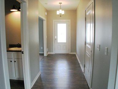 View from kitchen to front door. Door in left is half bath.