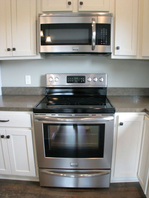 Stainless steel flat surface stove and built-in microwave.