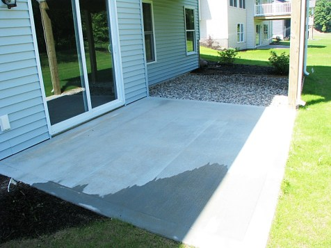 Slider leading to cement patio, stone under the covered deck