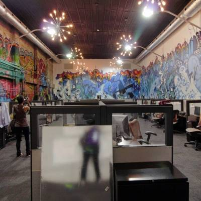 Colour graffiti surrounds the cubicles in this workspace