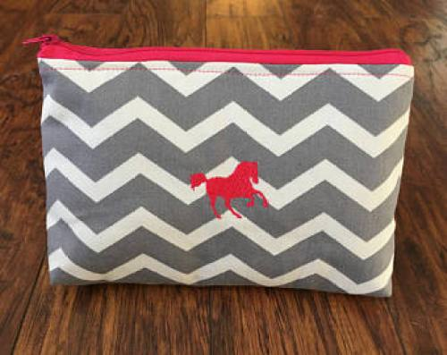 This is a cute gray and white cosmetic bag with a pink zipper and galloping pink horse. Perfect for a horse lover gift.