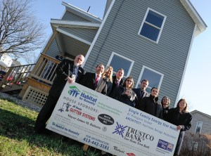 Habitat homeowner with sponsors in front of her new home.
