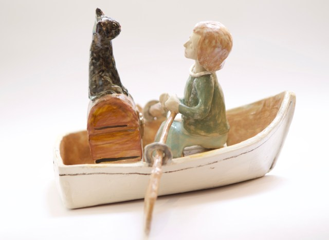 ceramic sculpture of a woman in a boat with a cat who is sitting on a treasure chest.  We suspect that the cat is a confidence trickster who has persuaded the lady to hand over her valuable possessions