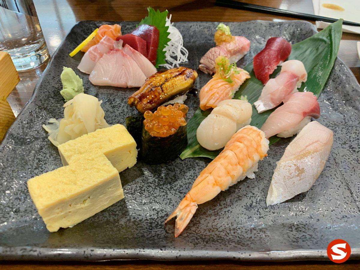 sake (salmon), maguro (tuna back), hamachi (yellowtail) sashimi, zuke chu toro (seared medium fatty tuna belly), maguro (tuna back), unagi (freshwater eel), sake yaki (grilled salmon), suzuki (sea bass), hotategai (scallop), hamachi (yellowtail), ebi (shrimp), saba (mackerel) nigiri, ikura (salmon roe) gunkan (battleship sushi) and tamago (egg omelet) plate