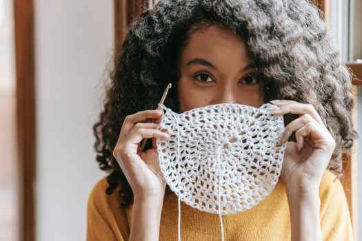 young woman covering mouth with white crochet napkin