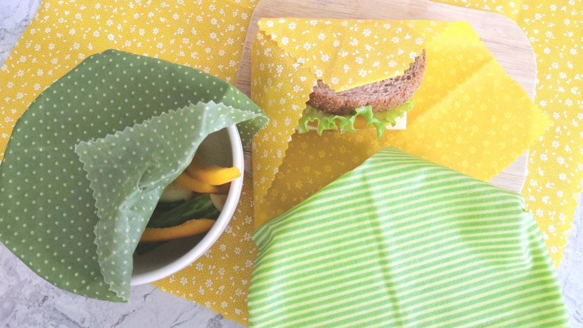 Sandwich, cucumber, bell pepper and a bowl wrapped in yellow and green beeswax wraps on a marble counter