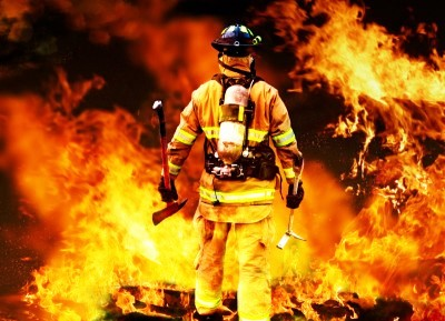 Colour photograph showing a firefighter at the scene of a fire