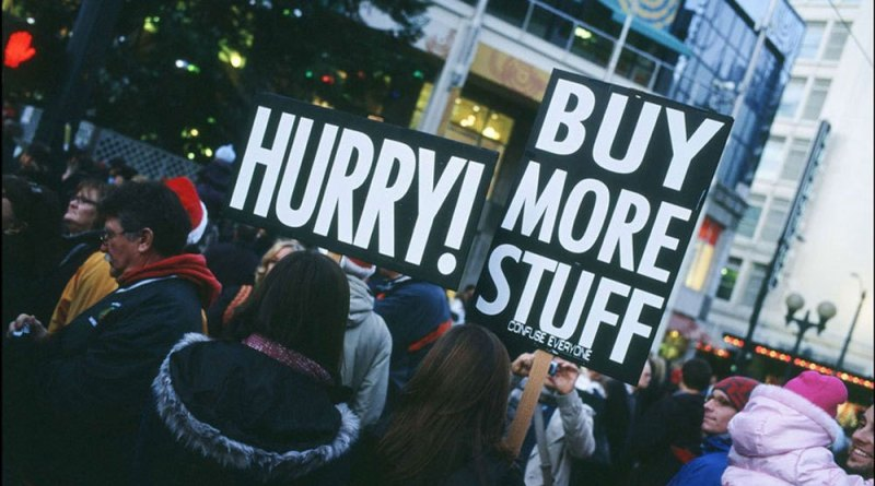 Placards at a rally stating 'hurry, buy more stuff'