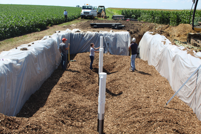 pit in farm field with woodchips being installed