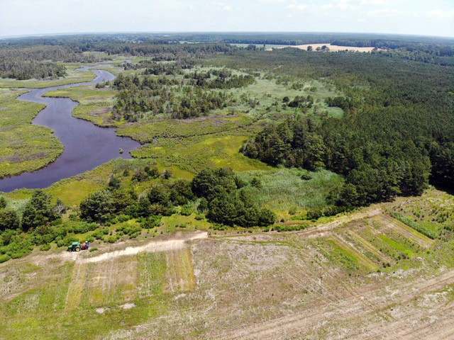 drone shot high above a farm field also showing some forest, marsh and a stream