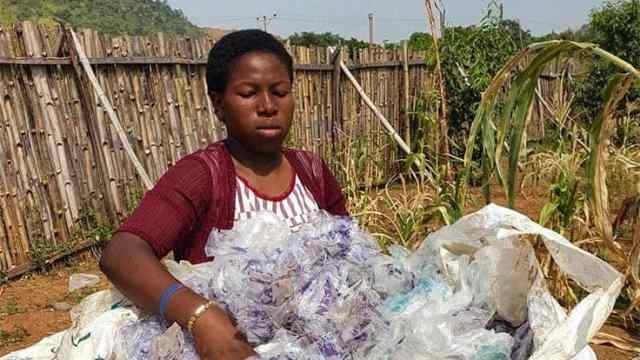 Nigerian woman collecting plastic waste