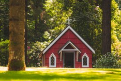 A small red church stands in a clearing of a forest.