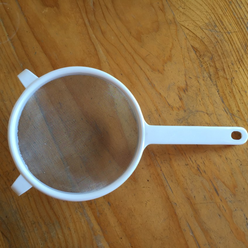 Sieve with white plastic rim and handle, on wooden surface