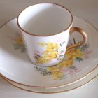 Small bone china tea cup with gold rim and yellow flower pattern on cup and saucer
