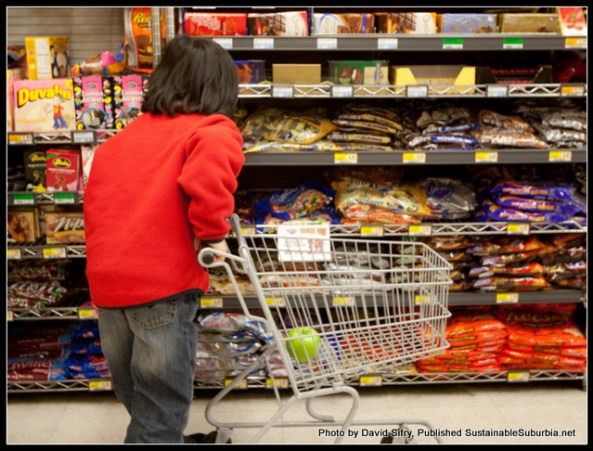 A boy, leaning a child-sized shopping trolley, with his back to the camera, standing in front of a supermarket shelf full of confectionary, bent over slightly towards the shelves in a focused pose.