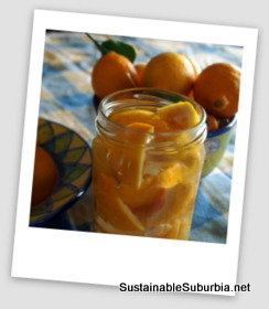 lemons soaking in a jar of white vinegar, with more lemons in a bowl in the background
