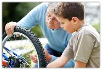 a child and his grandfather examine a bike wheel